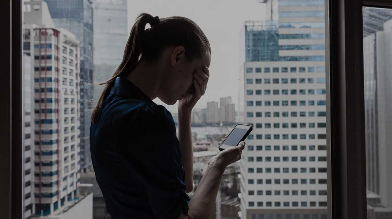 Stock image depicting a woman standing in front of a window holding a cell phone in her right hand and covering her eyes with her left hand.