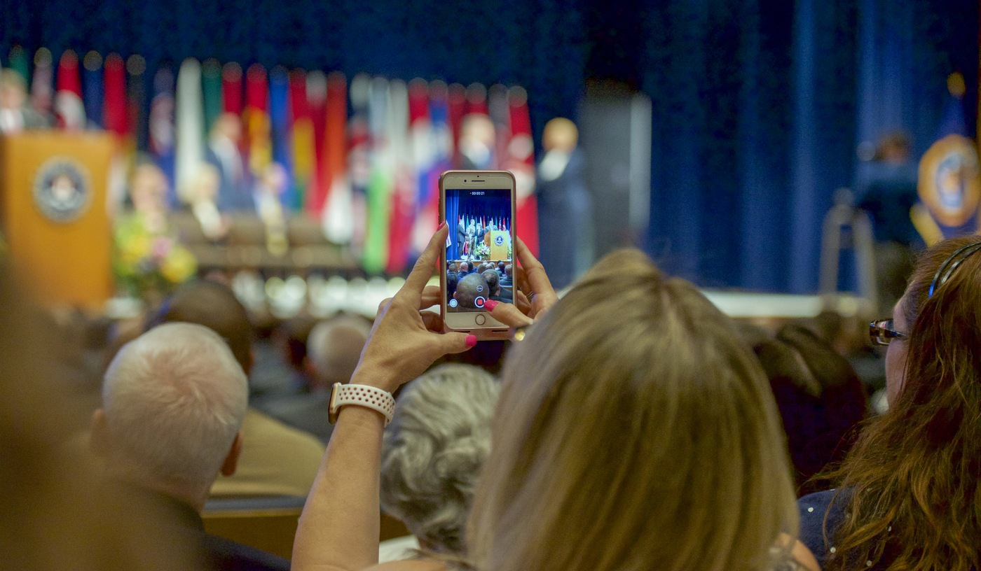Family member taking video at the National Academy Graduation