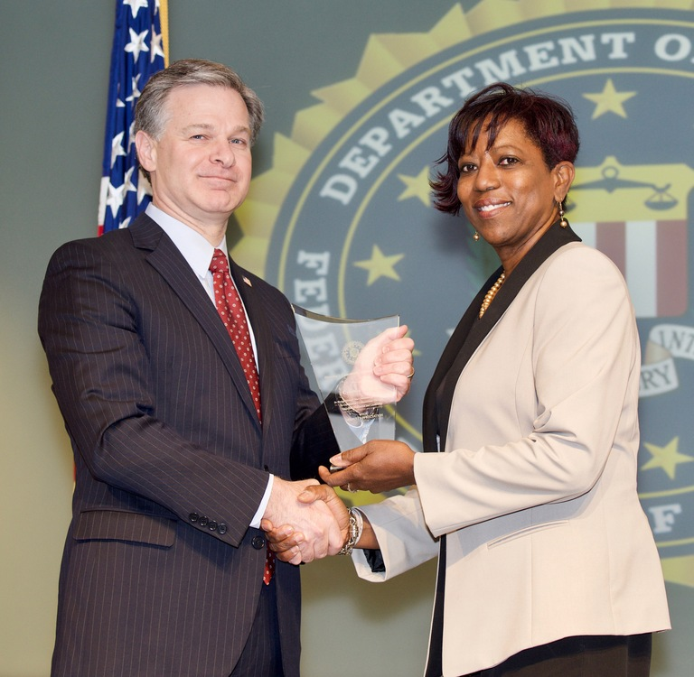 FBI Director Christopher Wray presents El Paso Division recipient Cynthia Horton with the Director's Community Leadership Award (DCLA) at a ceremony at FBI Headquarters on April 20, 2018.