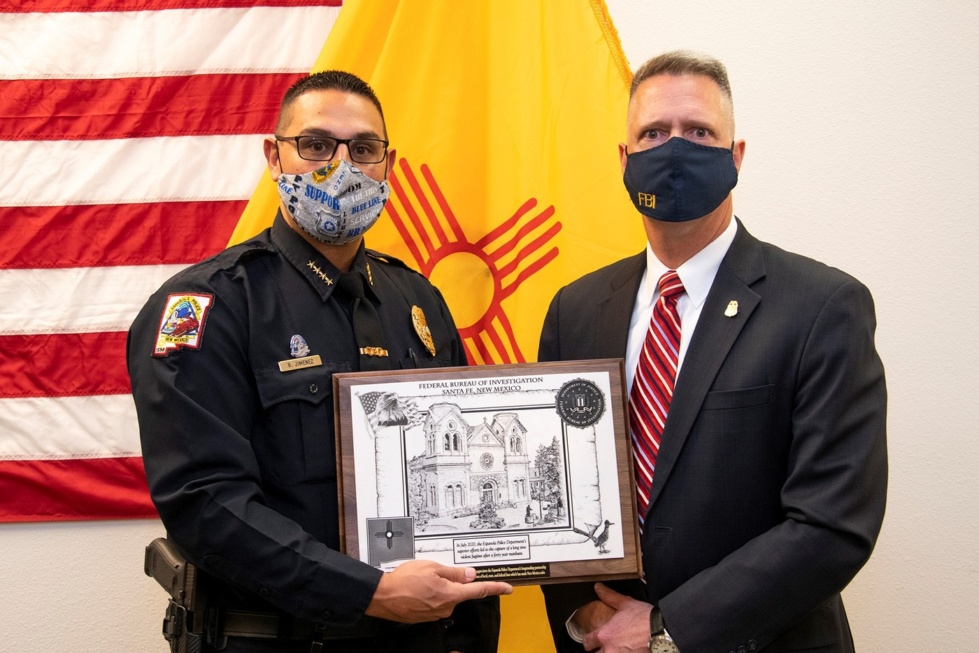 James Langenberg, Special Agent in Charge of the Albuquerque FBI Division, presented a plaque to Española Police Chief Roger Jimenez.