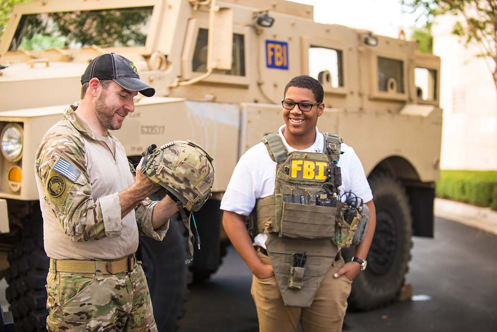 A student in FBI Tampa's Future Agents in Training program watches an agent demonstrate his equipment.