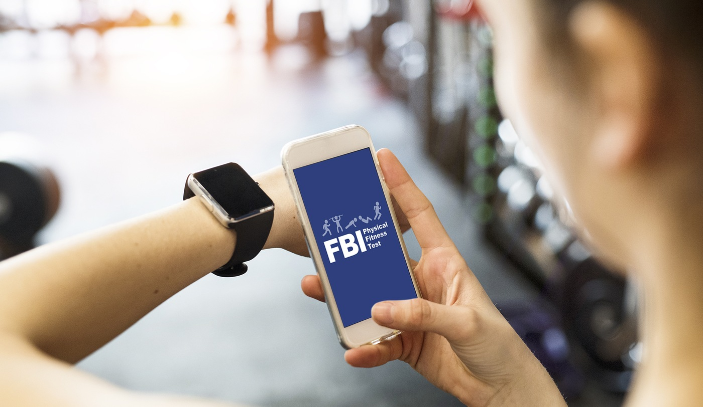 Stock image of a woman in a gym holding a smartphone displaying the FBI Physical Fitness Test app home screen while looking at her fitness watch.