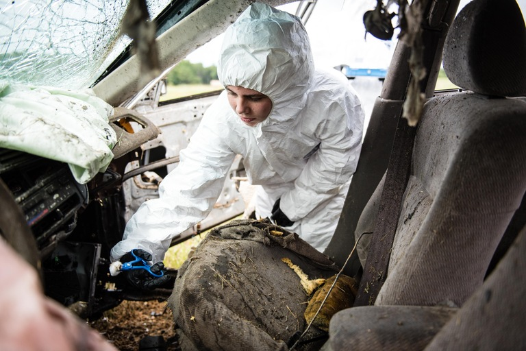 A Future Agents in Training (FAIT) participant collects an evidence sample after a simulated explosive detonated inside a vehicle near the FBI's Training Academy in Quantico, Virginia in August 2016.