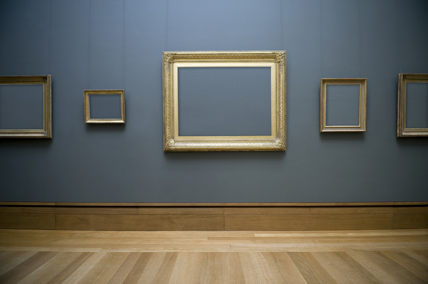 Stock image depicting an art gallery wall with multiple empty frames.