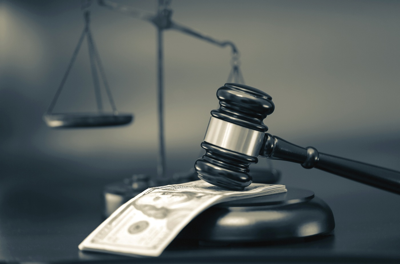Stock photo depicting money and a gavel, on the scales of justice.