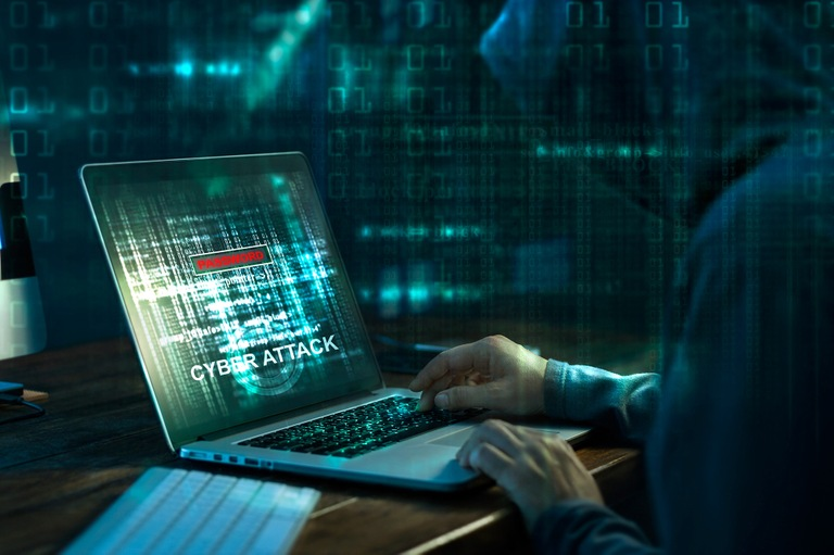Stock image depicting a hooded computer hacker using a laptop to conduct a cyber attack with code on the screen and in foreground and background of image.