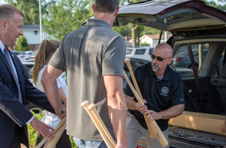 FBI Chicago Special Agent Brian Brusokas hands out baseball bats seized during a sports memorabilia fraud investigation for distribution to inner-city youth baseball leagues in Chicago on July 10, 2018.