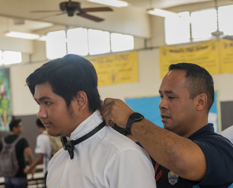 "Anson ""Kaipo"" Paiva, a member of the Honolulu Police Department's community policing team, helps a Waipahu High School freshman prepare for a presentation to community leaders."