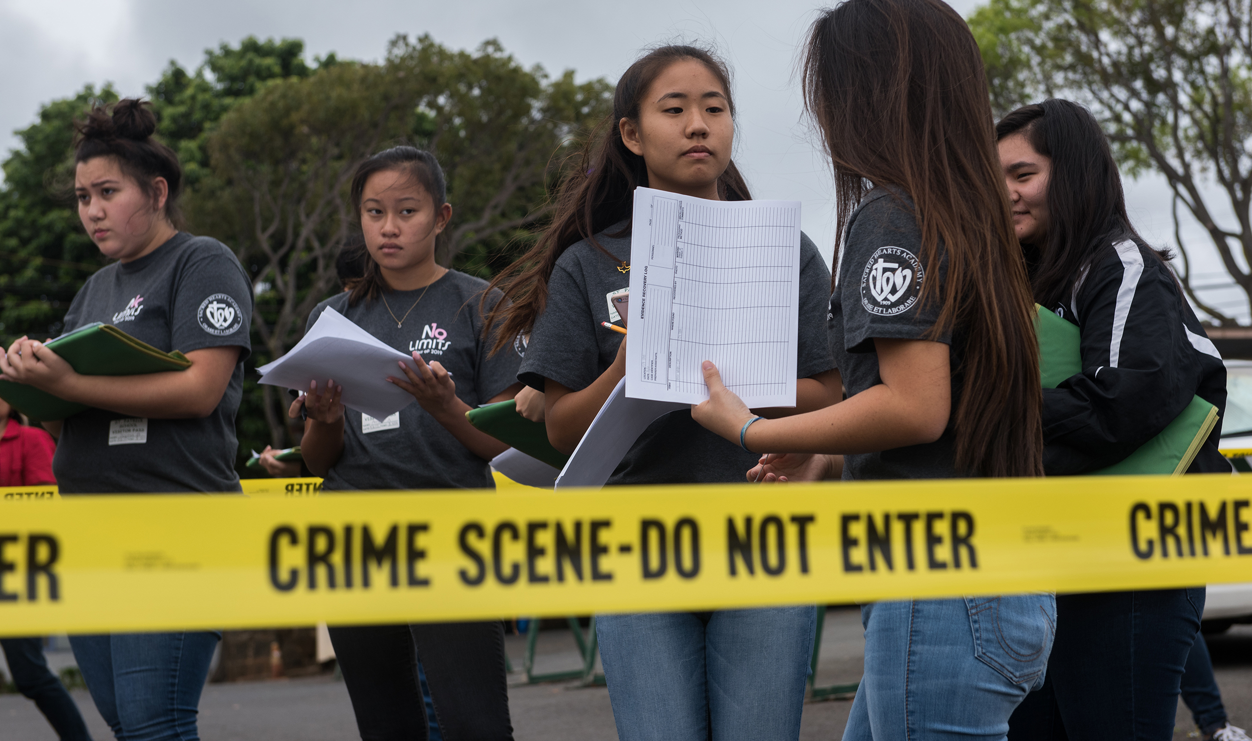 Students from Sacred Hearts Academy participating in FBI Honolulu's Adopt-a-School program in Hawaii learn how to process a mock crime scene.
