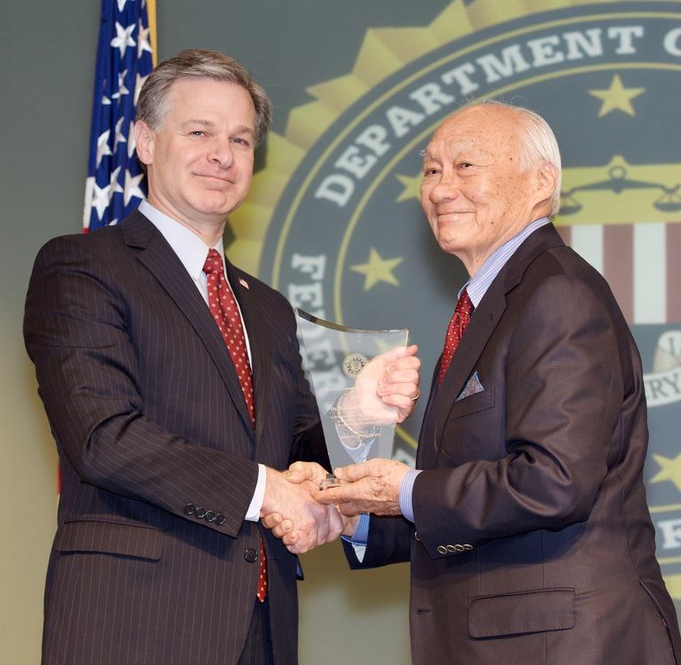 FBI Director Christopher Wray presents Honolulu Division recipient Edison Miyawaki with the Director's Community Leadership Award (DCLA) at a ceremony at FBI Headquarters on April 20, 2018.