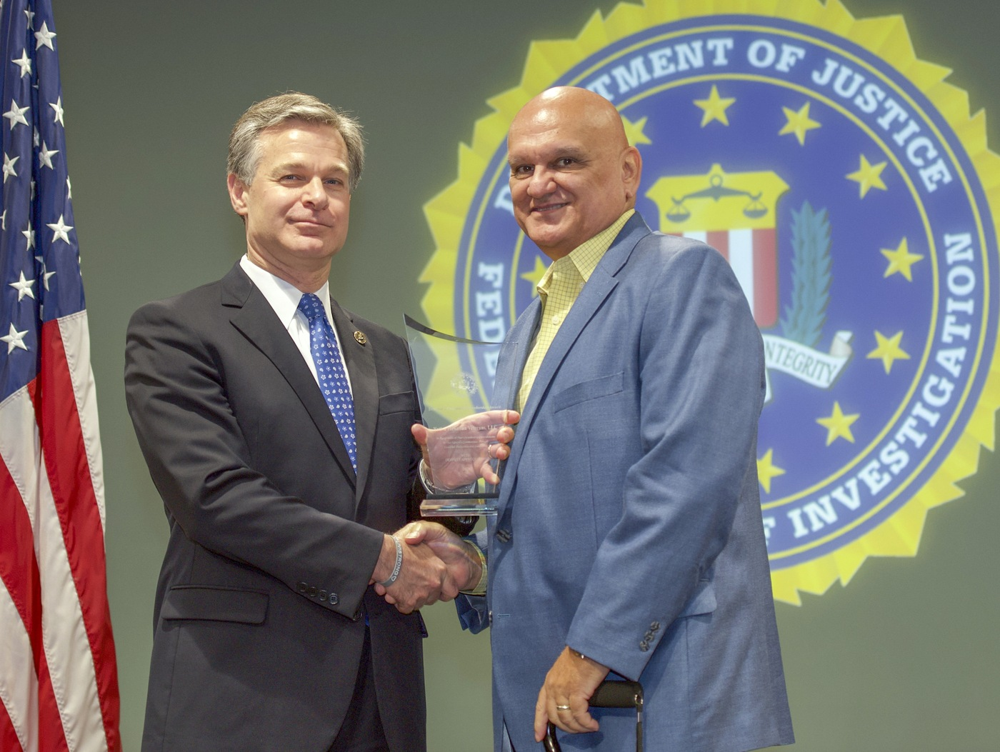 FBI Director Christopher Wray presents Honolulu Division recipient Native Hawaiian Veterans, LLC (represented by Raymond Jardine, Jr.) with the Director's Community Leadership Award (DCLA) at a ceremony at FBI Headquarters on May 3, 2019.