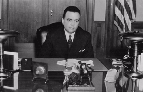 J. Edgar Hoover sits at the desk in his public office circa 1937. His private office is behind the two doors in the background.