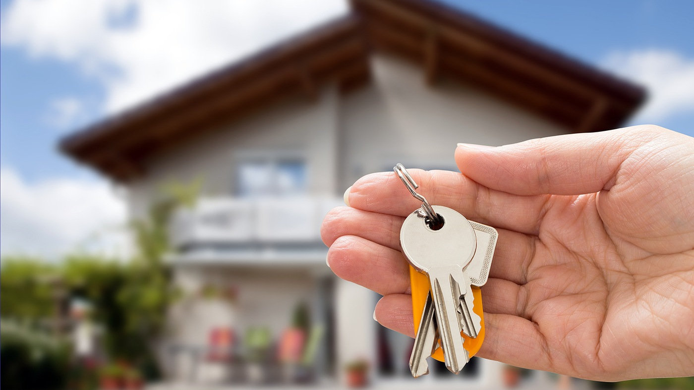 Stock image depicting a house in a blurred background and a hand holding keys in the foreground.