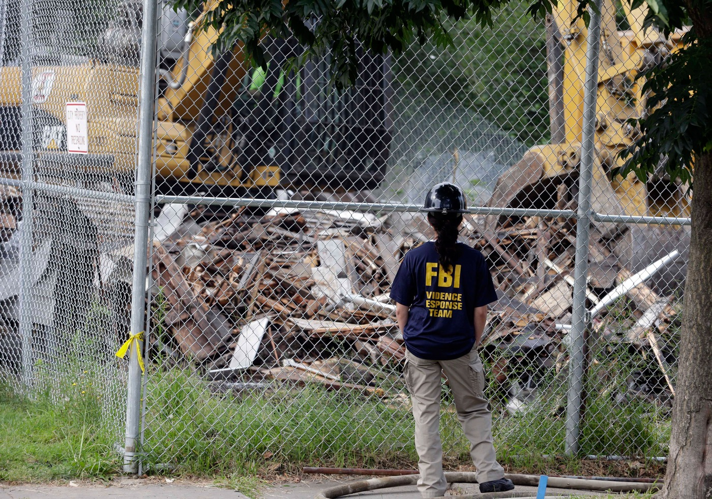 An FBI agent from our Evidence Response Team in Cleveland watches as the house where three women were held captive for more than a decade by Ariel Castro is demolished on August 7, 2013. The home was torn down as part of a plea agreement that spared Castro a possible death sentence; Castro was sentenced to life in prison without the possibility of parole. In the decade leading up to the rescue, the FBI worked hard with its partners to locate the missing women, following every lead and helping to publicize the kidnappings. Since their heroic escape from captivity, the FBI has assisted in numerous ways, lending its investigative, evidence response, behavioral, tactical, victim assistance services, and other capabilities to the investigation, which was prosecuted locally. AP Photo.