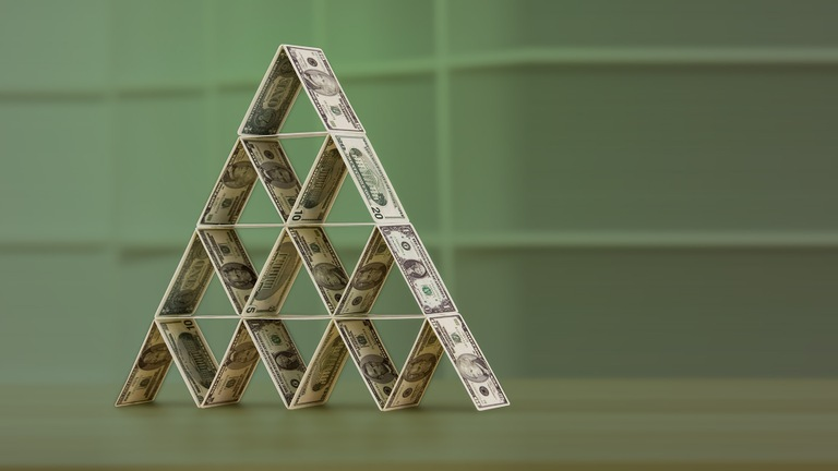 Stock image depicting a house of cards made of money representing a Ponzi scheme.