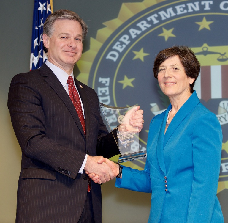FBI Director Christopher Wray presents Houston Division recipient Dena Marks Sokolow with the Director's Community Leadership Award (DCLA) at a ceremony at FBI Headquarters on April 20, 2018.