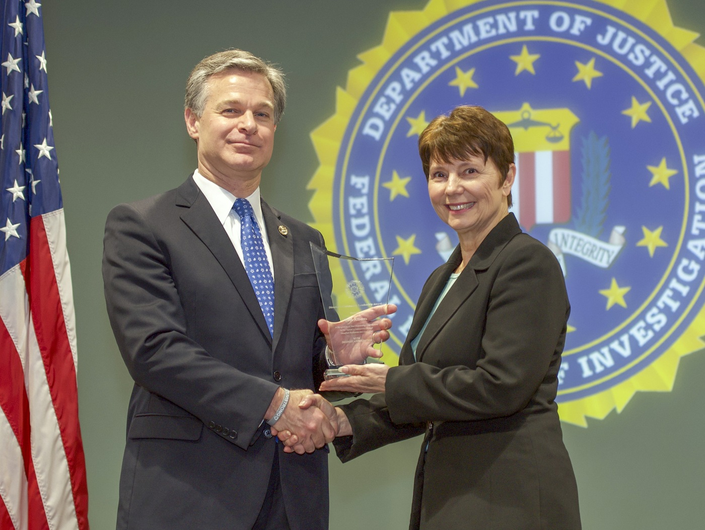 FBI Director Christopher Wray presents Houston Division recipient Beth Alberts with the Director's Community Leadership Award (DCLA) at a ceremony at FBI Headquarters on May 3, 2019.