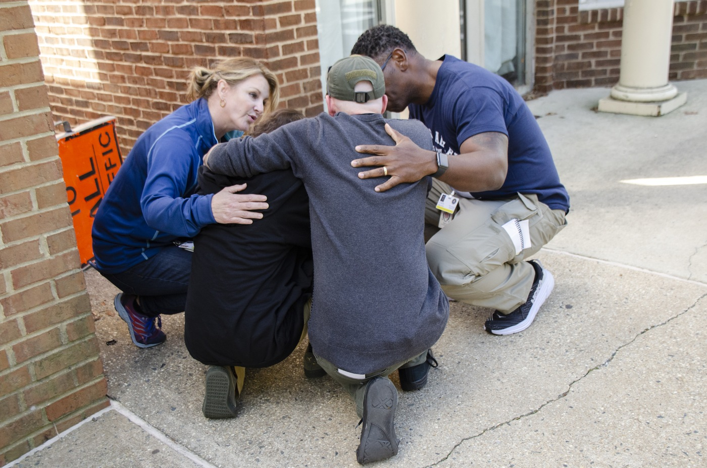 Kim Case (left), a victim advocate and consultant, and Curtis Graves (right), a commander in the Mobile Police Department in Alabama, console family members of a victim during a mock mass-casualty event September 25, 2019, at the FBI Training Academy in Quantico, Virginia. The exercise culminated ELEVATE-APB training for victim service providers.