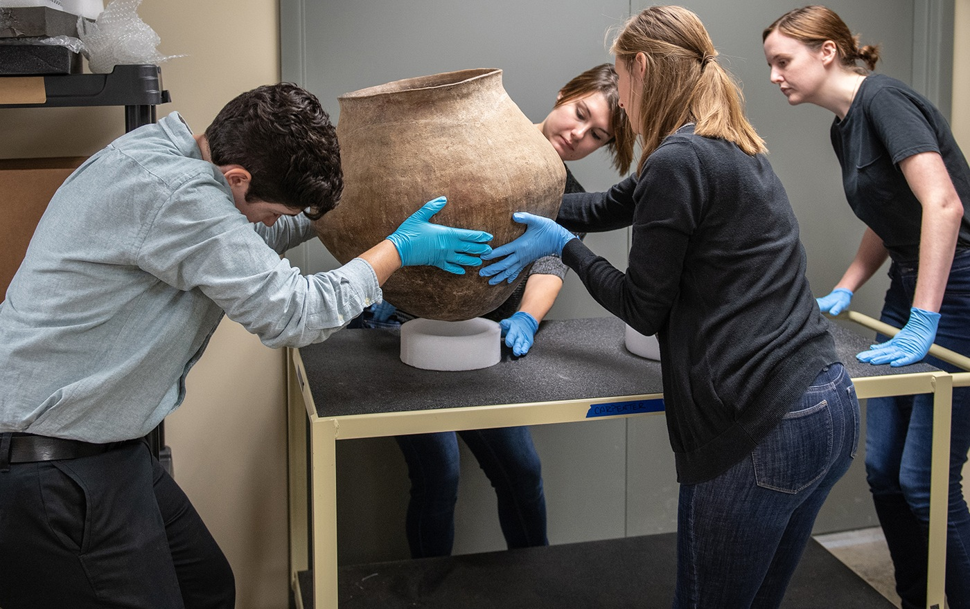 Graduate students handle a large piece of pottery that was among the thousands of items recovered by the FBI at Don Miller's home in 2014.