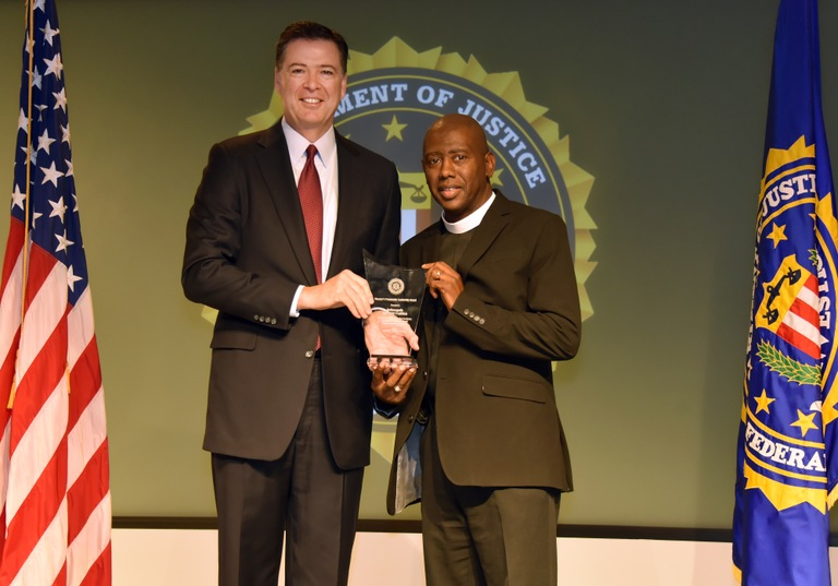 FBI Director James Comey presents Indianapolis Division recipient Indianapolis Ten Point Coalition (represented by Rev. Charles Harrison) with the Director's Community Leadership Award (DCLA) at a ceremony at FBI Headquarters on April 28, 2017.