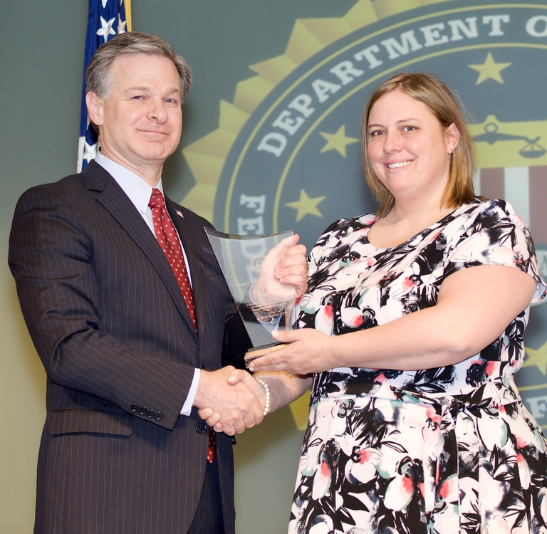 FBI Director Christopher Wray presents Indianapolis Division recipient Ascent 121 (represented by Megan Jessup) with the Director's Community Leadership Award (DCLA) at a ceremony at FBI Headquarters on April 20, 2018.