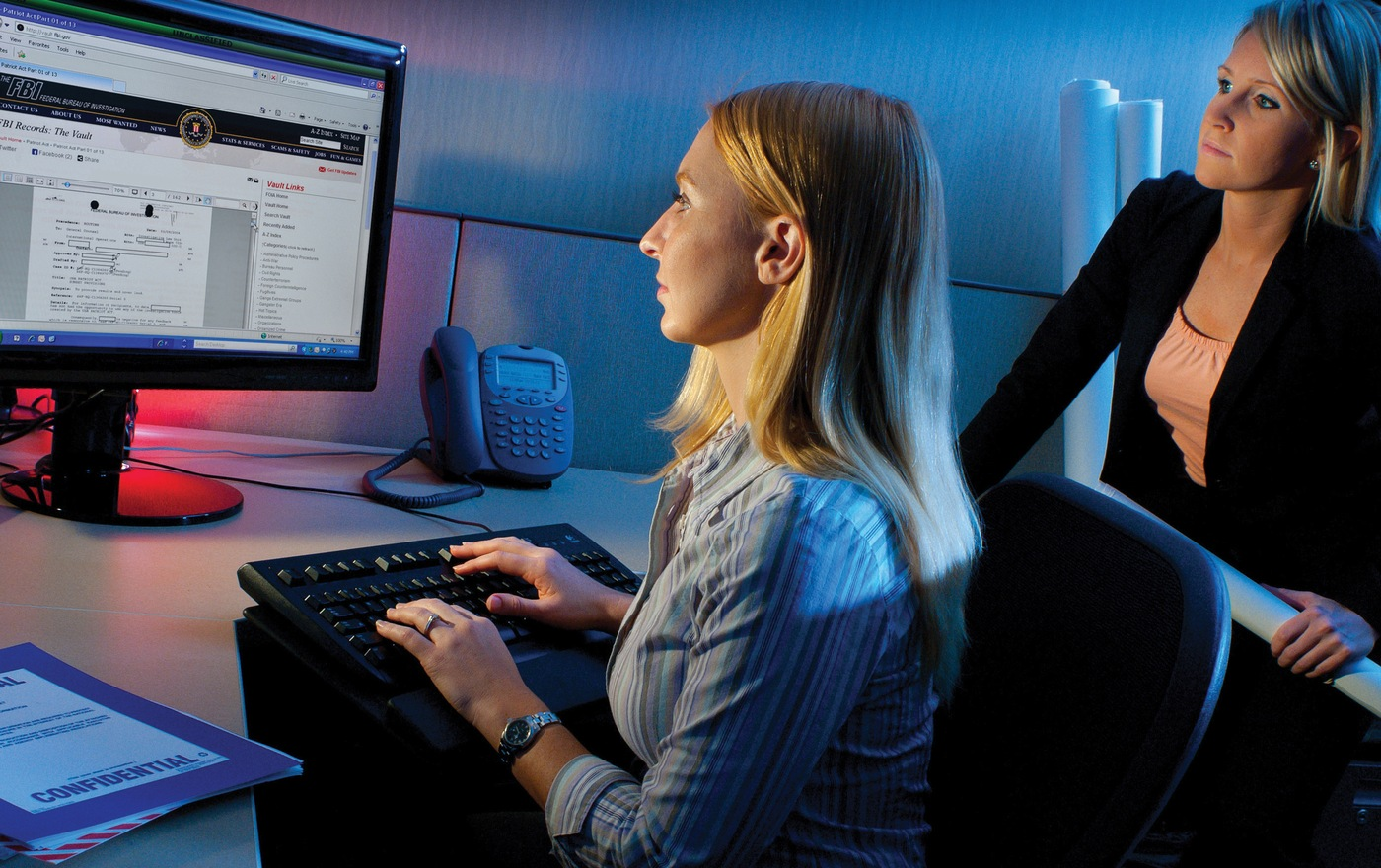 An FBI intelligence analyst works at a computer.