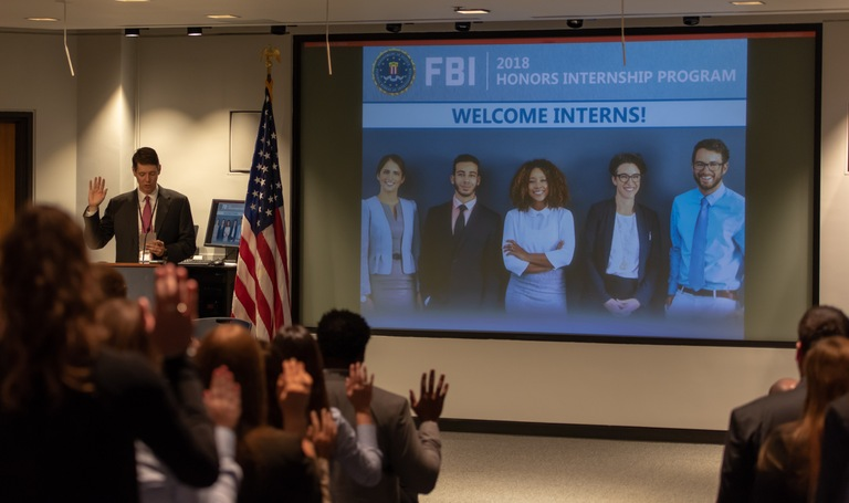 David Schlendorf, assistant director for the FBI's Human Resources Division, administers the oath of office to members of the Honors Internship Program at FBI Headquarters as they begin a 10-week summer work program at the Bureau.