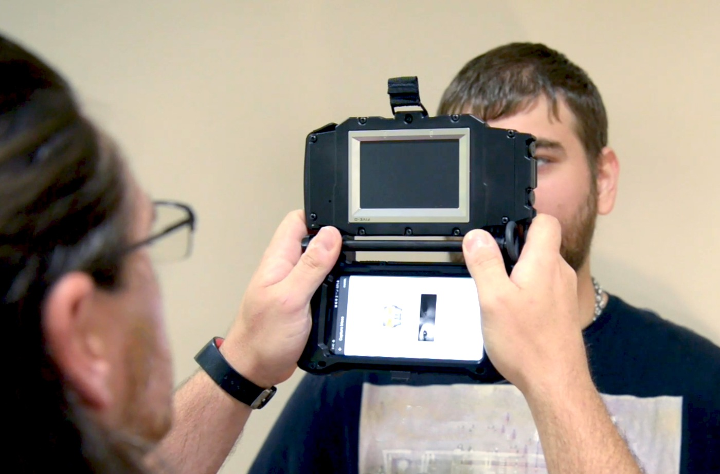 Two people demonstrate how a device is used to capture imagery of irises for the Next Generation Identification (NGI) Iris Service.