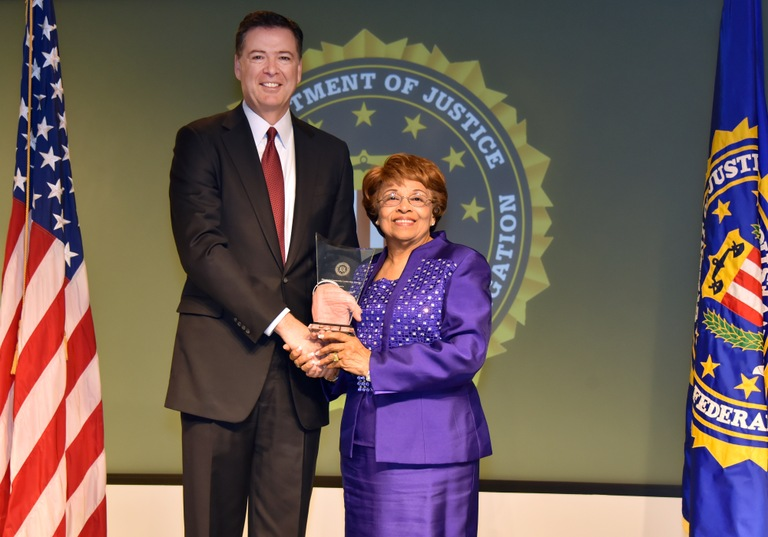 FBI Director James Comey presents Jackson Division recipient Flonzie Brown-Wright with the Director's Community Leadership Award (DCLA) at a ceremony at FBI Headquarters on April 28, 2017.