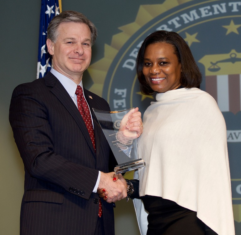 FBI Director Christopher Wray presents Jackson Division recipient the Mississippi Center for Excellence (represented by Ingrid Cloy) with the Director's Community Leadership Award (DCLA) at a ceremony at FBI Headquarters on April 20, 2018.