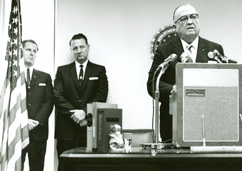 """FBI Director J. Edgar Hoover speaks at the opening of the Jackson Division on July 10, 1964 as newly minted Jackson Special Agent in Charge Roy K. Moore (far left) and trusted Hoover adviser Special Agent Cartha """"Deke"""" DeLoach look on."""