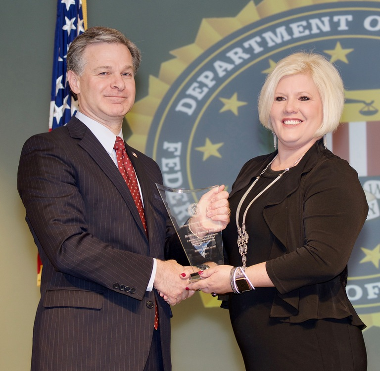FBI Director Christopher Wray presents Jacksonville Division recipient Reverend Jennifer Beagle with the Director's Community Leadership Award (DCLA) at a ceremony at FBI Headquarters on April 20, 2018.