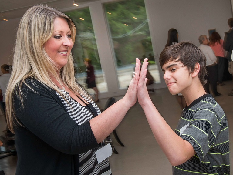 "Student artwork on display at the ""Human Trafficking: Do You See It?"" exhibit hosted by the Northeast Florida Human Trafficking Coalition. Student artist Corey Kreisel (right) high-fives Lori Armstrong, co-chair of the Northeast Florida Human Trafficking Coalition. 