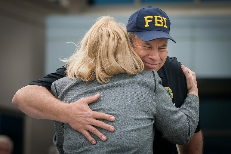 Pete Miller (right), president of the FBI Jacksonville Citizens Academy Alumni Association, receives a hug to go along with a recognition award from Ann Dugger, executive director of the Justice Coalition, during the first annual FAN luncheon.
