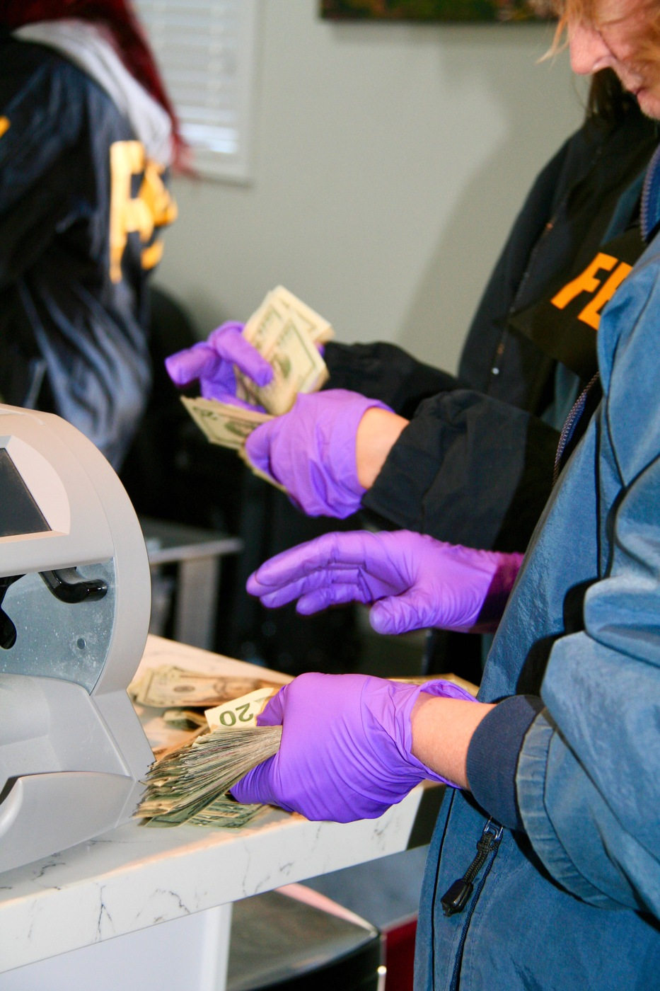 Agents count U.S. currency during execution of search warrant in L.A. in March 2020 and seized approximately $22,000 in cash.