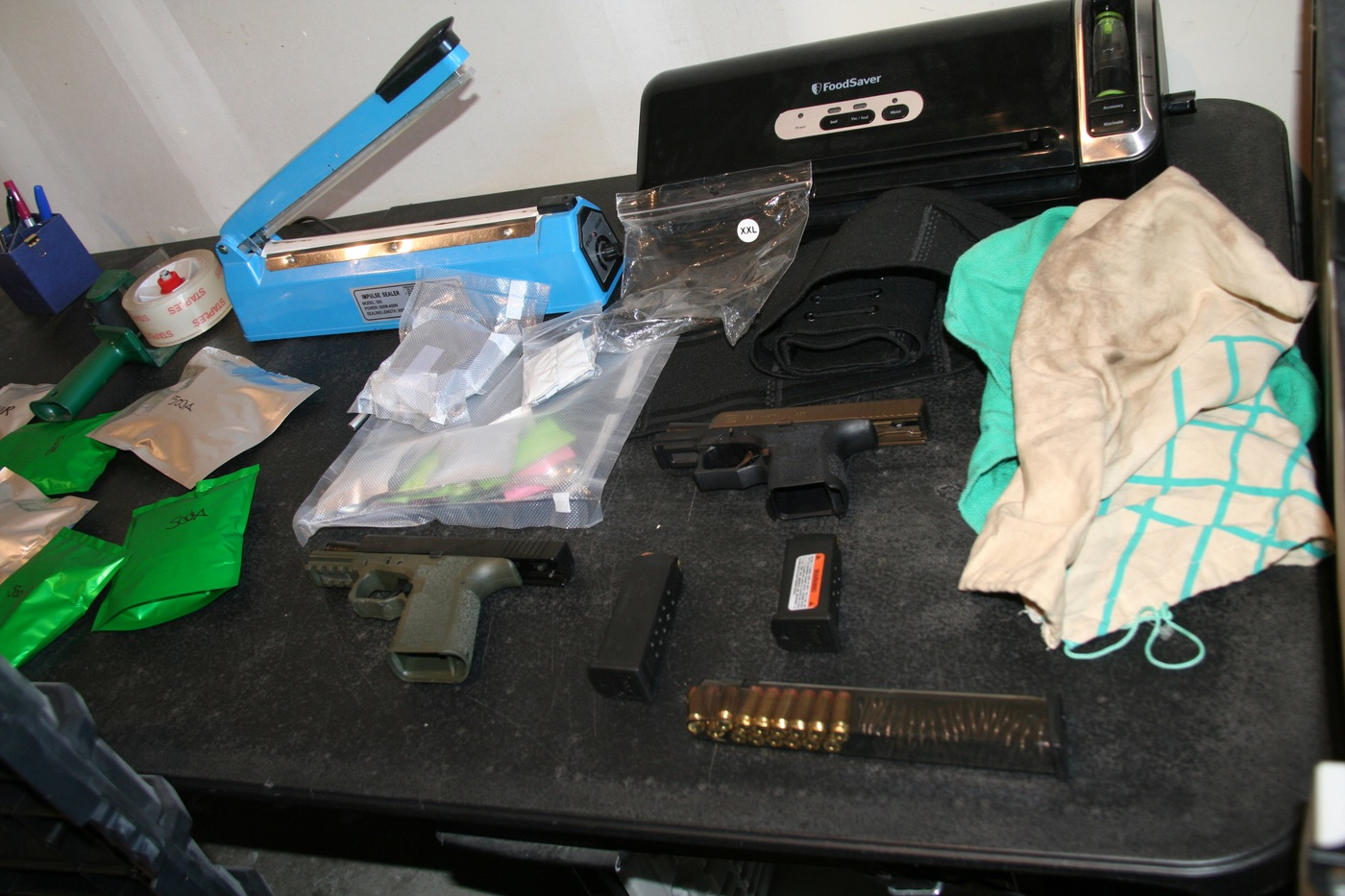 Firearms, drug packages and heat sealing equipment found and seized by JCODE Task Force in March 2020.