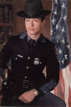 Undated portrait of Virginia State Police Trooper Johnny Bowman in uniform with American flag. Bowman was murdered at his home on August 19, 1984; the case remains unsolved.