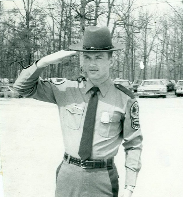 Undated black and white photo of Virginia State Police Trooper Johnny Bowman in uniform and saluting. Bowman was murdered at his home on August 19, 1984; the case remains unsolved.