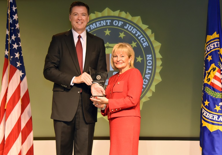 FBI Director James Comey presents Kansas City Division recipient Judy Overton with the Director's Community Leadership Award (DCLA) at a ceremony at FBI Headquarters on April 28, 2017.