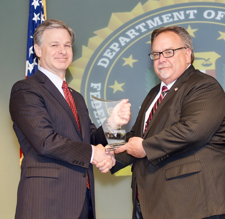 FBI Director Christopher Wray presents Kansas City Division recipient Taking It to the Streets (represented by Scott LaMaster) with the Director's Community Leadership Award (DCLA) at a ceremony at FBI Headquarters on April 20, 2018.