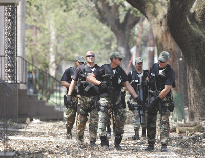 An FBI SWAT Team helps local law enforcement on the streets of New Orleans in the wake of Hurricane Katrina in 2005. AP Photo.