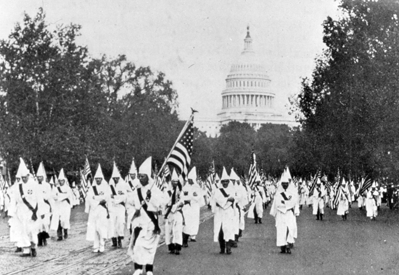 Robed members of the KKK marching down Pennsylvania Avenue in Washington, D.C., with American flags and the U.S. Capitol in the background.