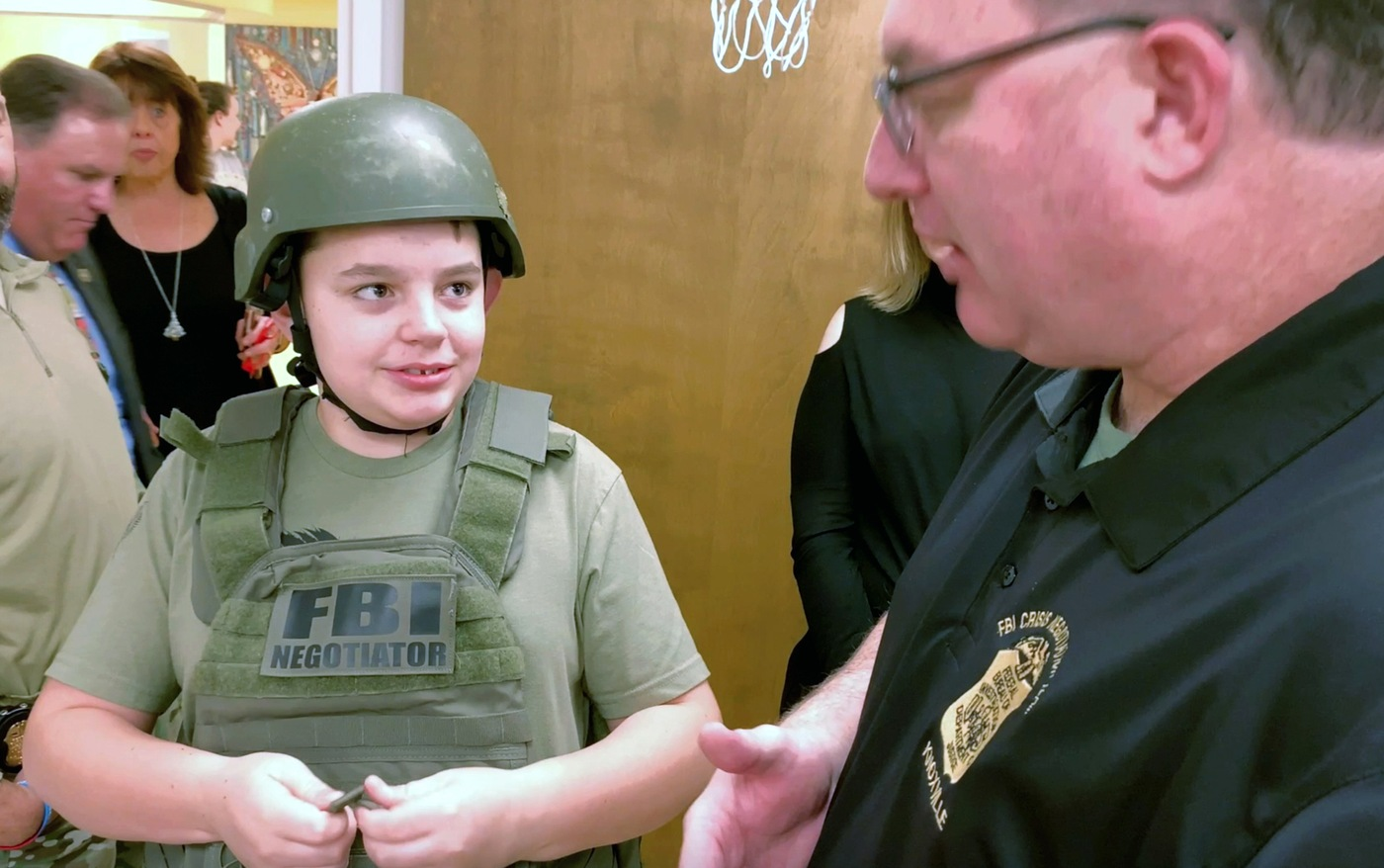 A patient at East Tennessee Children's Hospital wears FBI gear while talking with an FBI crisis negotiator during a visit by the Knoxville Field Office and the FBI Knoxville Citizens Academy Alumni Association on December 6, 2019.