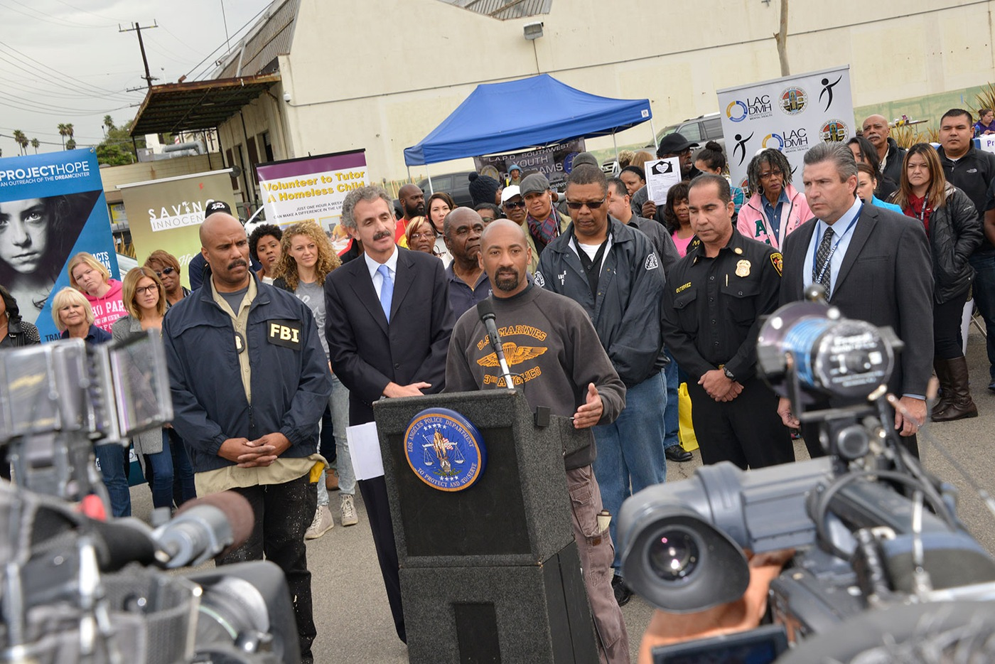 Los Angeles Police Department Detective Cedric Washington discusses the Community Impact Initiative as FBI Los Angeles Assistant Special Agent in Charge Robert Clark (far left) and other partners look on.