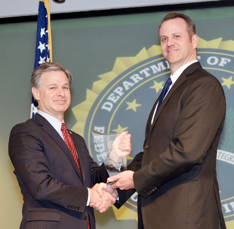 FBI Director Christopher Wray presents Las Vegas Division recipient Las Vegas Clear Channel Outdoor (represented by Adam Barthelmess) with the Director's Community Leadership Award (DCLA) at a ceremony at FBI Headquarters on April 20, 2018.