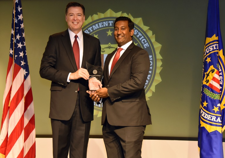 FBI Director James Comey presents Little Rock Division recipient Jason Chacko with the Director's Community Leadership Award (DCLA) at a ceremony at FBI Headquarters on April 28, 2017.