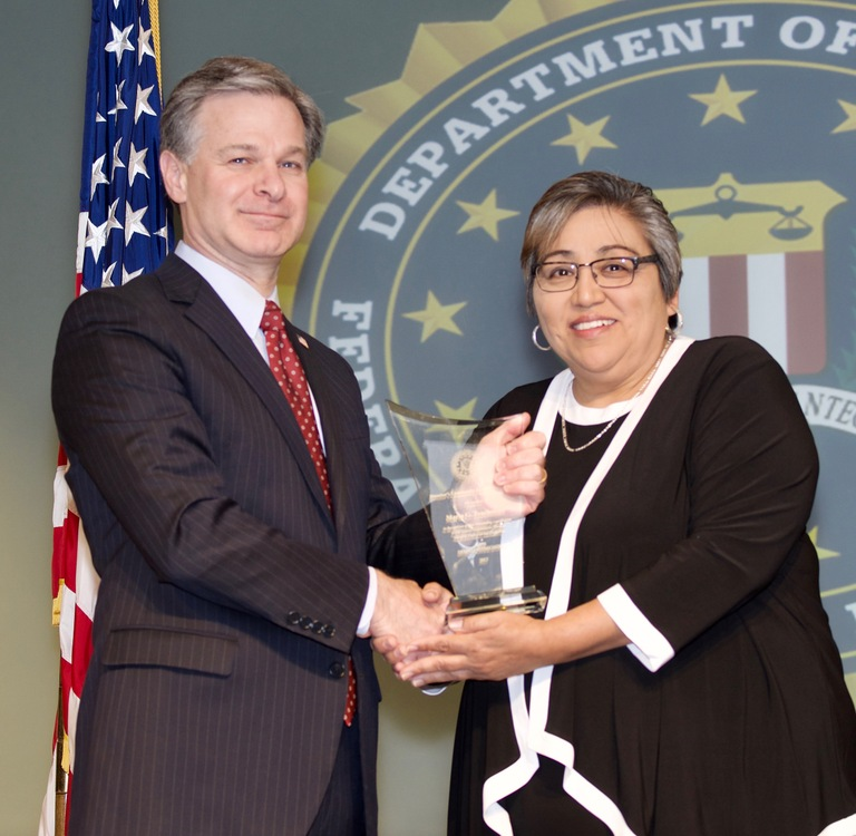 FBI Director Christopher Wray presents Little Rock Division recipient Maria Touchstone with the Director's Community Leadership Award (DCLA) at a ceremony at FBI Headquarters on April 20, 2018.