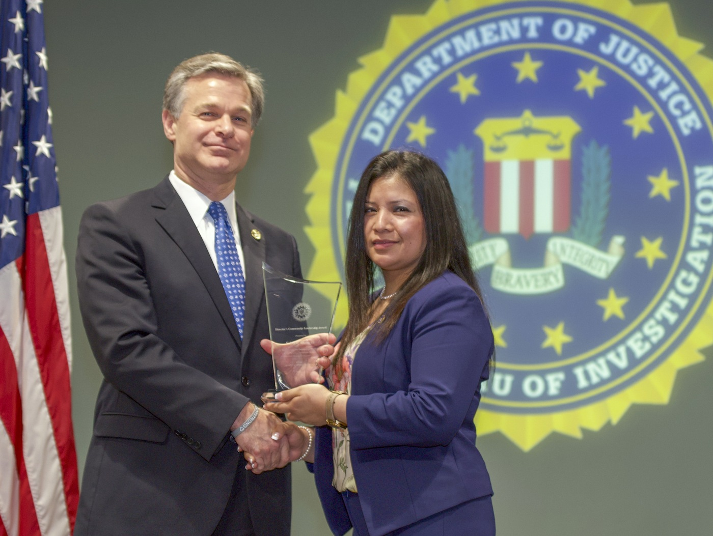 FBI Director Christopher Wray presents Little Rock Division recipient Edna I. Ramirez with the Director's Community Leadership Award (DCLA) at a ceremony at FBI Headquarters on May 3, 2019.