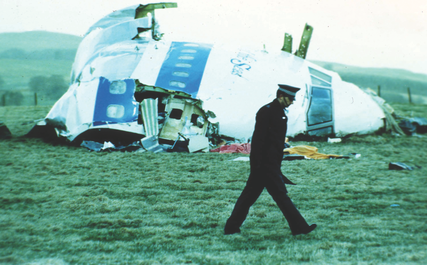 A Scottish police officer searches for clues near the nose of the downed Pan Am Flight 103 on a farm outside of Lockerbie in December 1988. AP Photo.