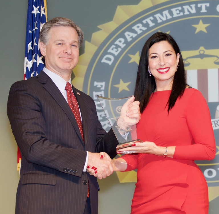 FBI Director Christopher Wray presents Los Angeles Division recipient Tina Aldatz with the Director's Community Leadership Award (DCLA) at a ceremony at FBI Headquarters on April 20, 2018.